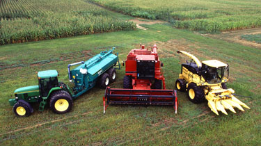 Three pieces of farm equipment in a field