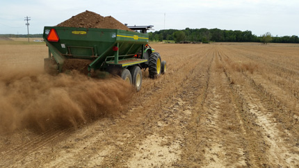 Applying chicken litter to field using mechanical spreader