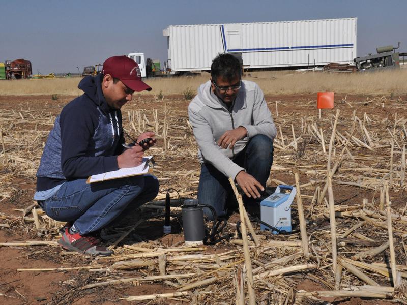 Dos hombres recogiendo medidas del suelo en el campo.