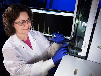 Un científico que lleva bata de laboratorio, protección ocular y guantes azules inserta un pequeño frasco de líquido transparente en un cromatógrafo.  Detrás de ella hay una pantalla de computadora que muestra un gráfico.