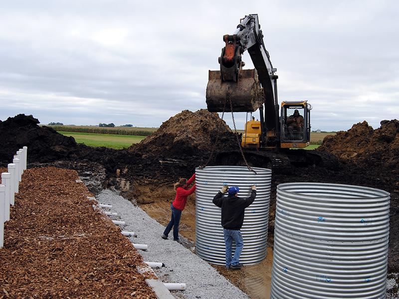 Una excavadora instala alcantarillas en un área de campo con gente esperando