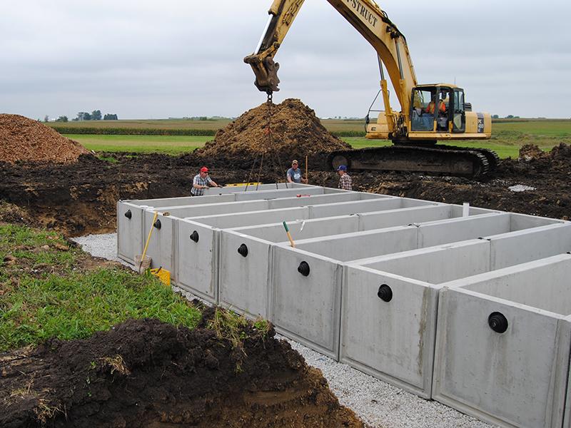 La excavadora coloca barreras de hormigón para revestir la zanja del biorreactor en un campo agrícola