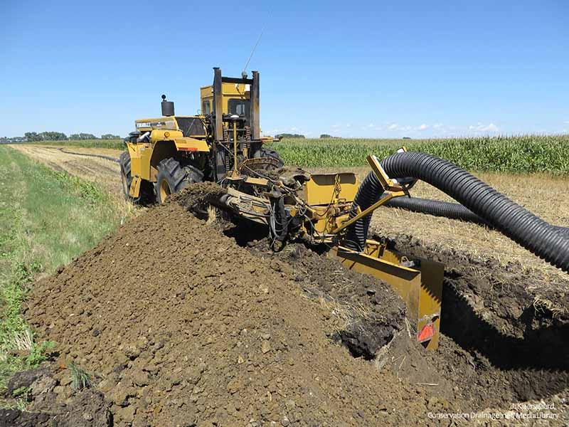 Máquina para hacer zanjas de drenaje de baldosas excavando en un campo